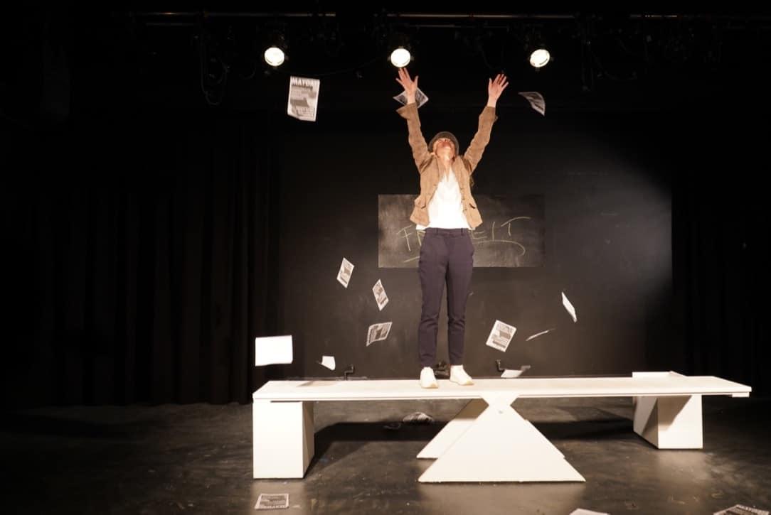 Foto aus Name: Sophie Scholl. Schauspielerin wirft Papier in die Luft, im Hintergrund ein Schild mit der Aufschrift Freiheit.