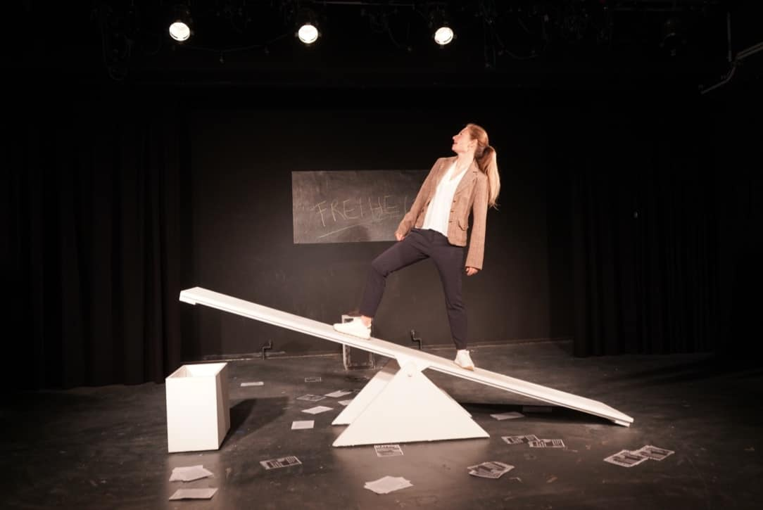 Foto aus Name: Sophie Scholl. Schauspielerin balanciert auf Wippe, im Hintergrund ein Schild mit der Aufschrift Freiheit.