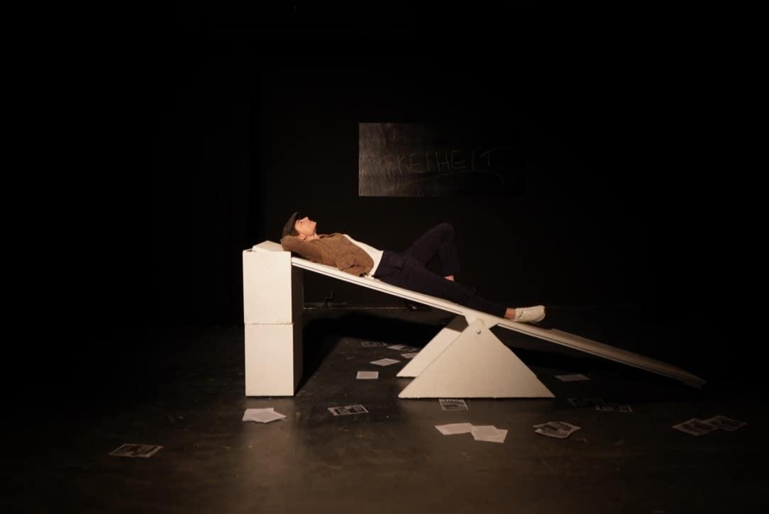 Foto aus Name: Sophie Scholl. Schauspielerin liegt auf einer Wippe, im dunklen Hintergrund ein Schild mit der Aufschrift Freiheit.